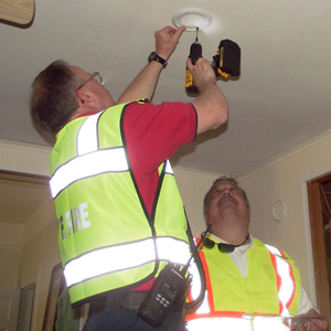 two people installing a smoke detector