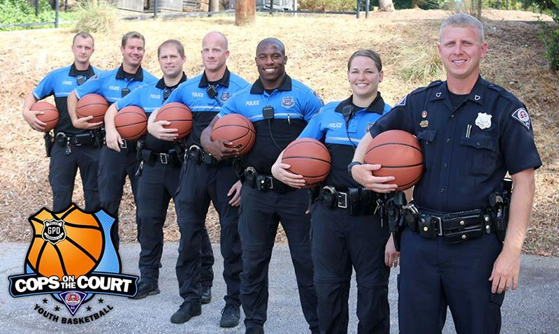 Police officers holding basketballs